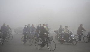 People ride along a street on a smoggy day in Daqing